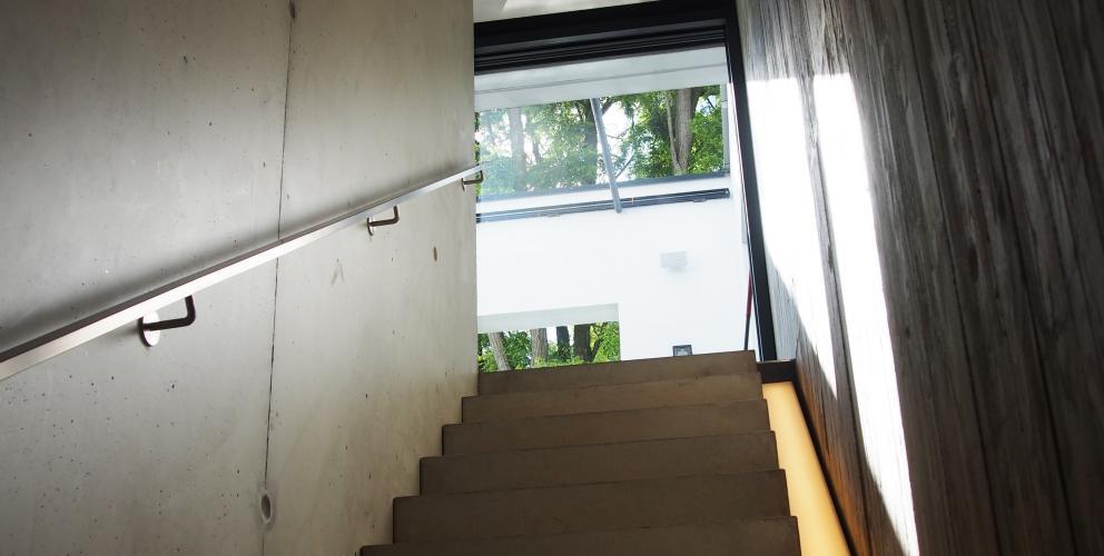 Projet CS - L'escalier menant au sous-sol confronte béton lisse et béton brute dans un jeu de matière subtil